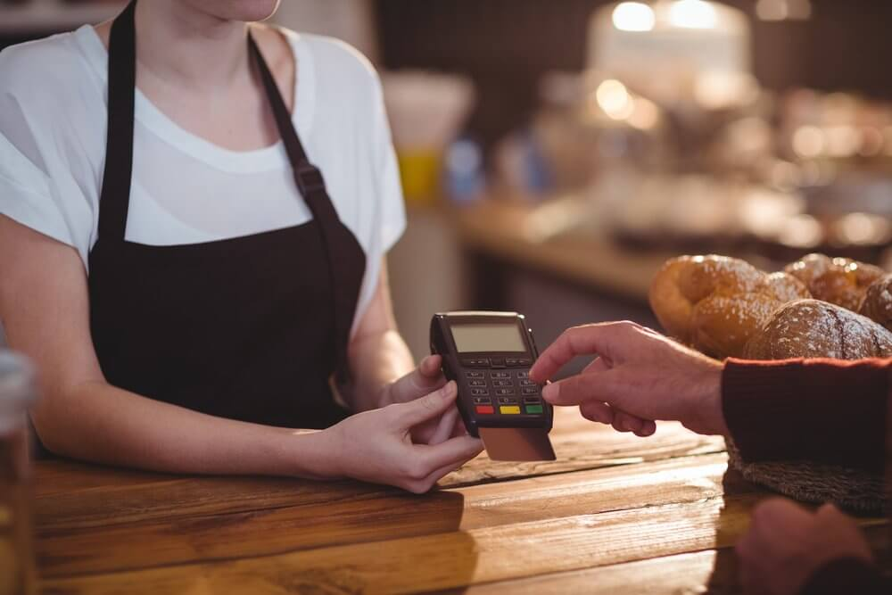 Customer entering pin number into machine at counter in cafe-1